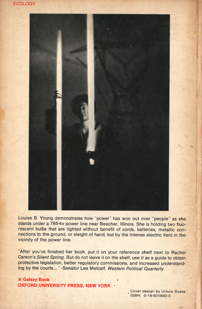 """The text maybe too small so I put it again in this caption: """"Louise B. Young demonstrates how """"power"""" has won out over """"people"""" as she stands under a 765kv power line near Beecher, Illinois. She is holding two fluorescent bulbs that are lighted without benefit of cords, batteries, metallic connections to the ground, or sleigh of hand, but by the intense electric field in the vicinity of the power line."""""""