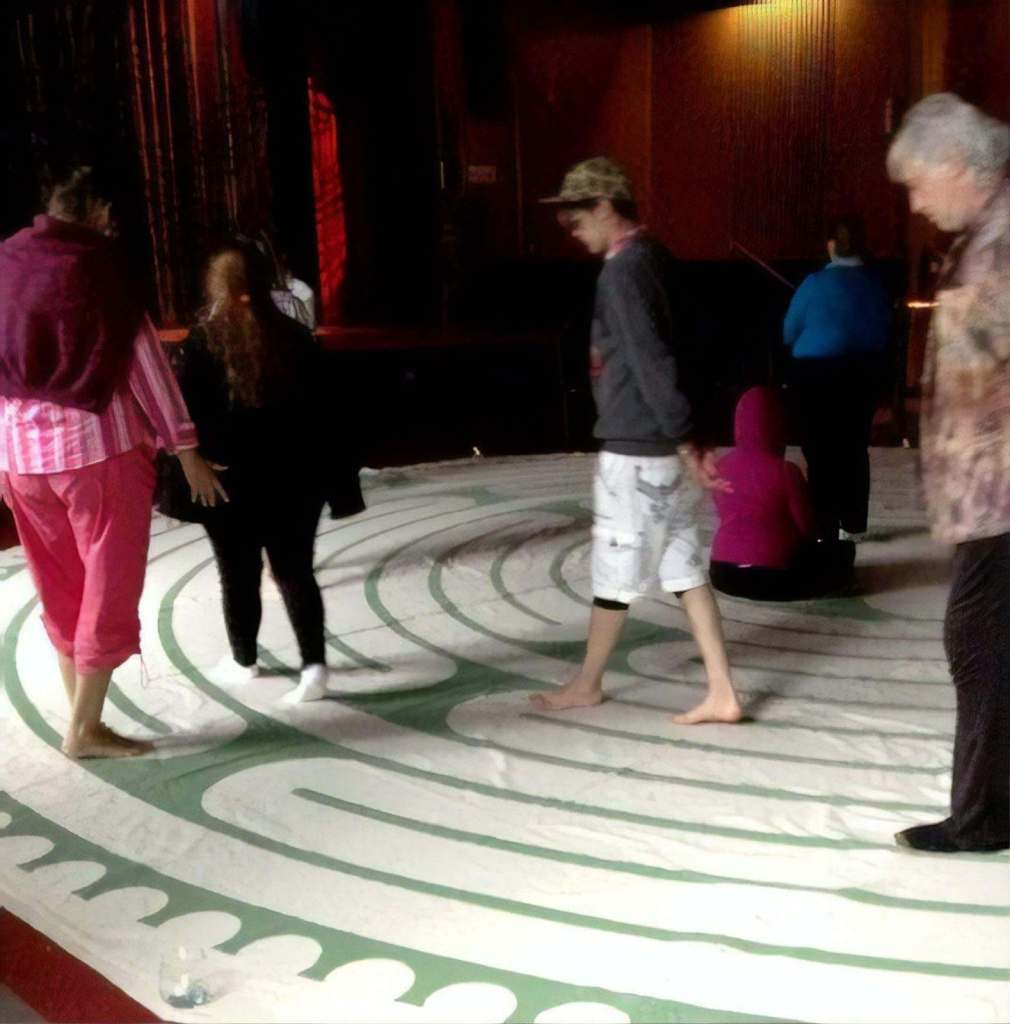 People walking on a hand-painted canvas Labyrinth