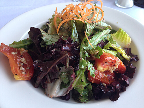 La Ronde Mixed Greens (mesculin greens, oven roasted roma tomatoes, carrot threads, raspberry balsamic dressing) at La Ronde Revolving Restaurant (Small - $9).