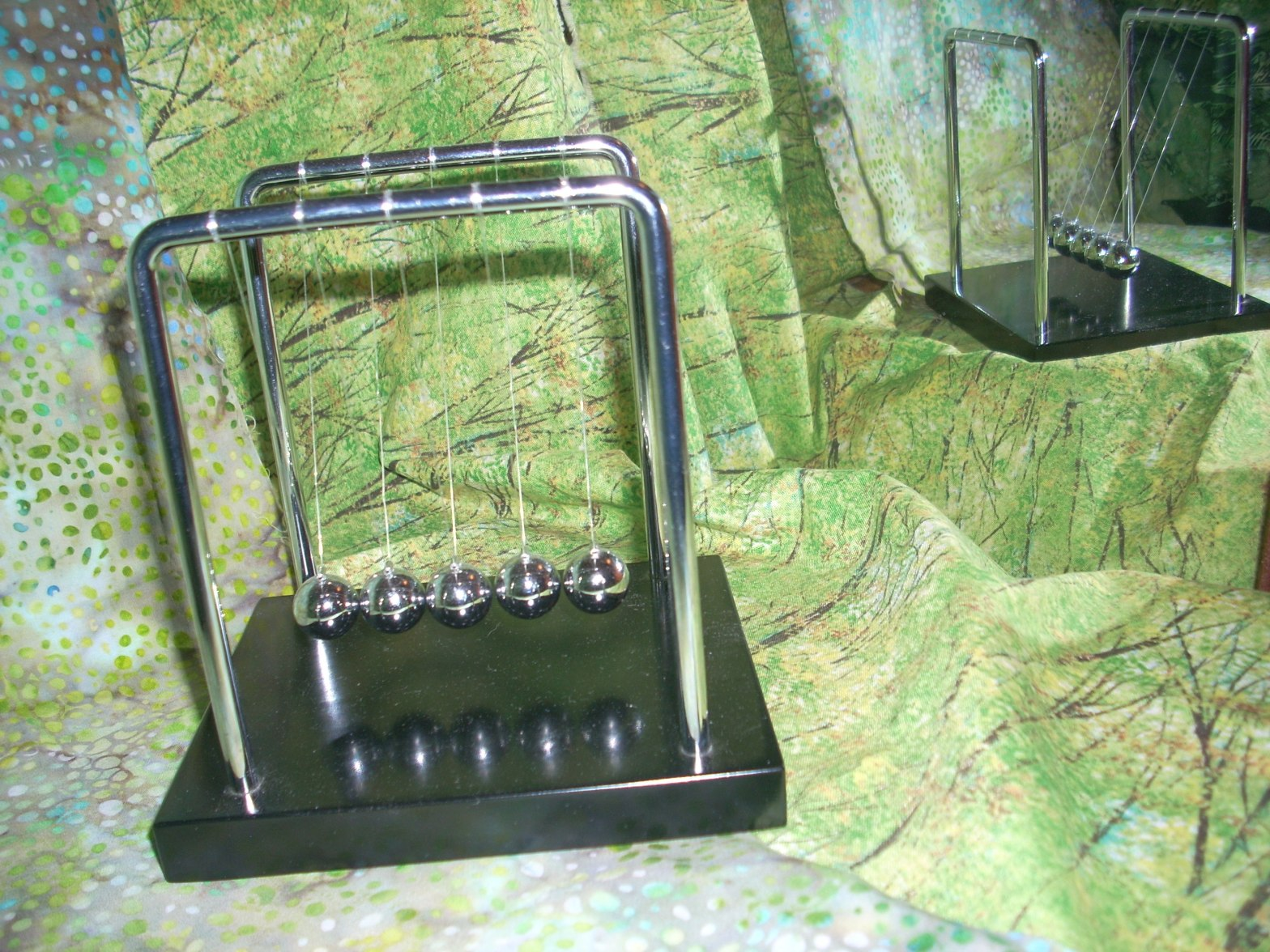 Photo of a Newton's Cradle, reflected in a mirror. Are you like a Newton's Cradle?