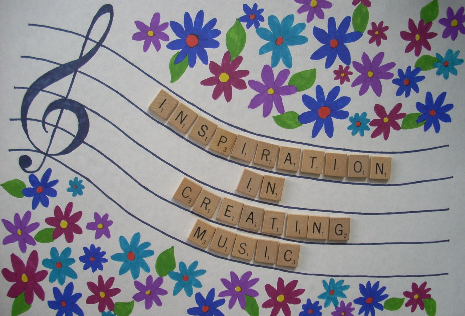 """Image of a treble cleff and music staff with Scrabble Tiles spelling """"Inspiration in Creating Music"""". It is surrounded by colorful flowers."""