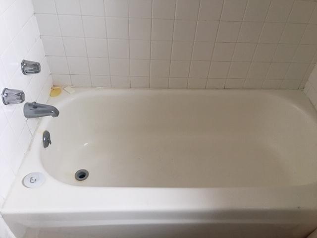 white bathtub with tile