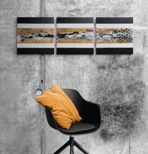 Tableau abstrait moderne triptyque fait main doré noir et blanc accroché sur un mur gris avec en décoration une chaise noire et un coussin jaune moutarde