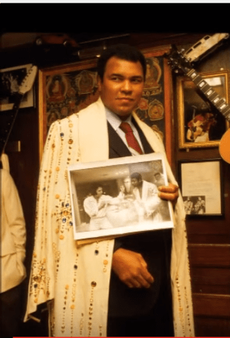 Ali holding photo of him and Elvis with the robe