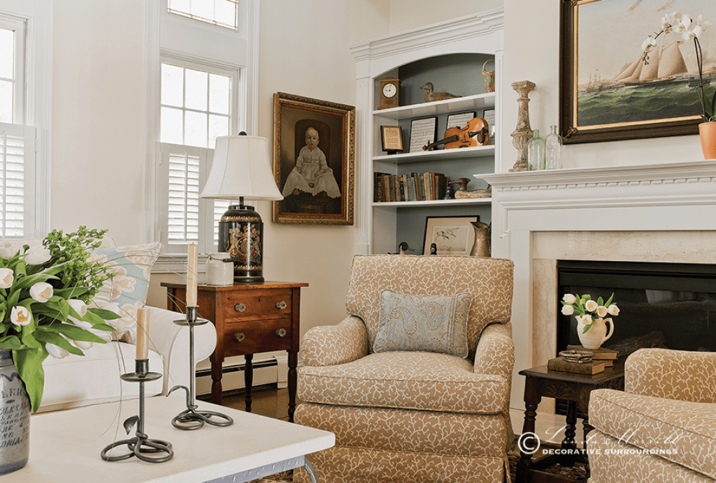 A coastal home in Duxbury, MA filled with antiques and comfortable arm chairs in front of the fireplace
