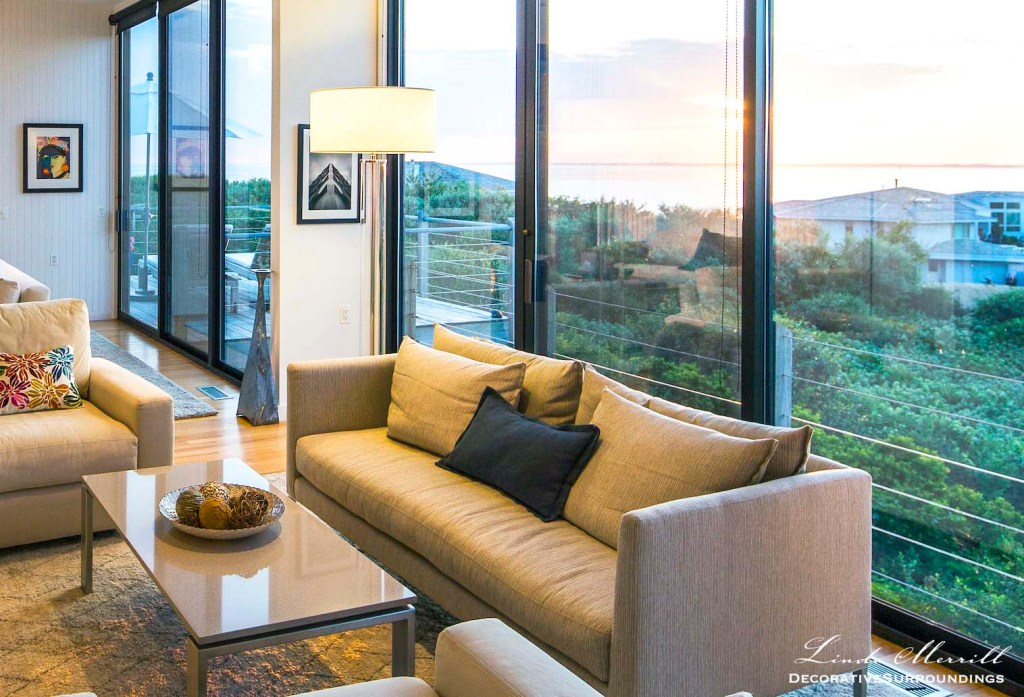 Modern beach house living room in Truro, Massachusetts with off white sofas overlooking the Atlantic Ocean.