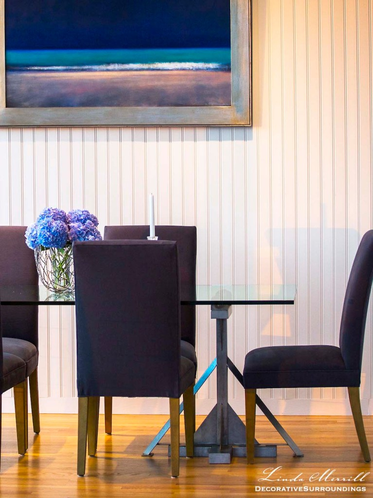 Modern beach house dining room in Truro, Massachusetts with blue chairs, modern glass dining table and beadboard wall.