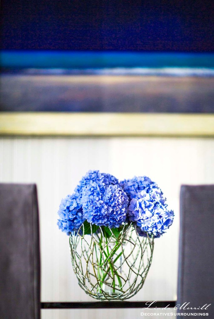 Modern beach house Truro, Massachusetts dining room blue hydrangea detail with art in the background.