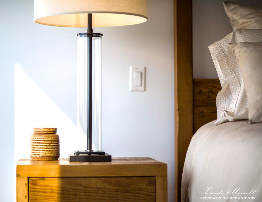 Modern beach house bedroom in Truro, Massachusetts with rustic wood side table and beige bedding. Restoration Hardware table lamp.