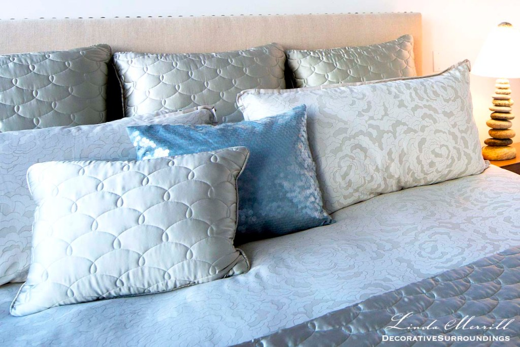 Modern beach house bedroom in Truro, Massachusetts with blue silk bedding, beige linen headboard with nailhead trim.