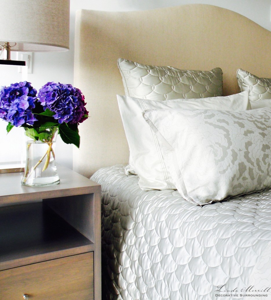 Modern Beach House bedroom in Truro, Massachusetts gray silk bedding, side table and purple hydrangea