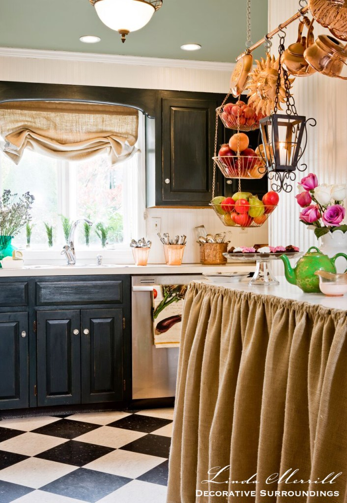 French country kitchen with burlap counter skirt, copper pots, green painted cabinets, black and white checkerboard floors.
