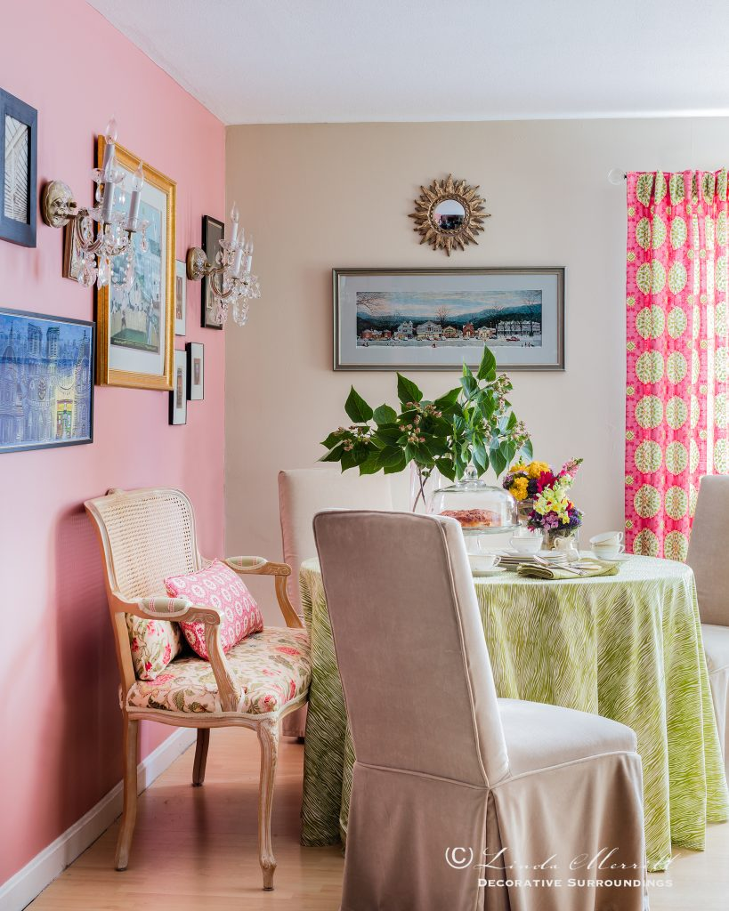 Design by Linda Merrill Decorative Surroundings: Colorful waterfront cottage Dining space with pink accent wall, slipcovered chairs, table skirt, french settee, pink and green colors