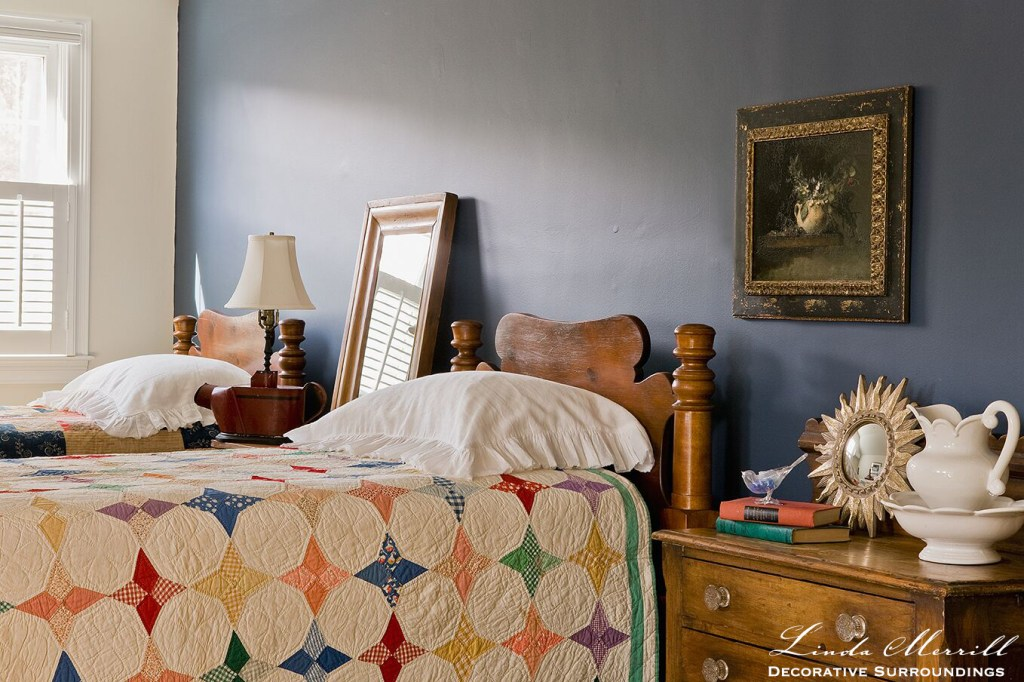 Coastal Home bed room in Duxbury MA white dark blue wall, colorful antique quilts antique furniture fine art