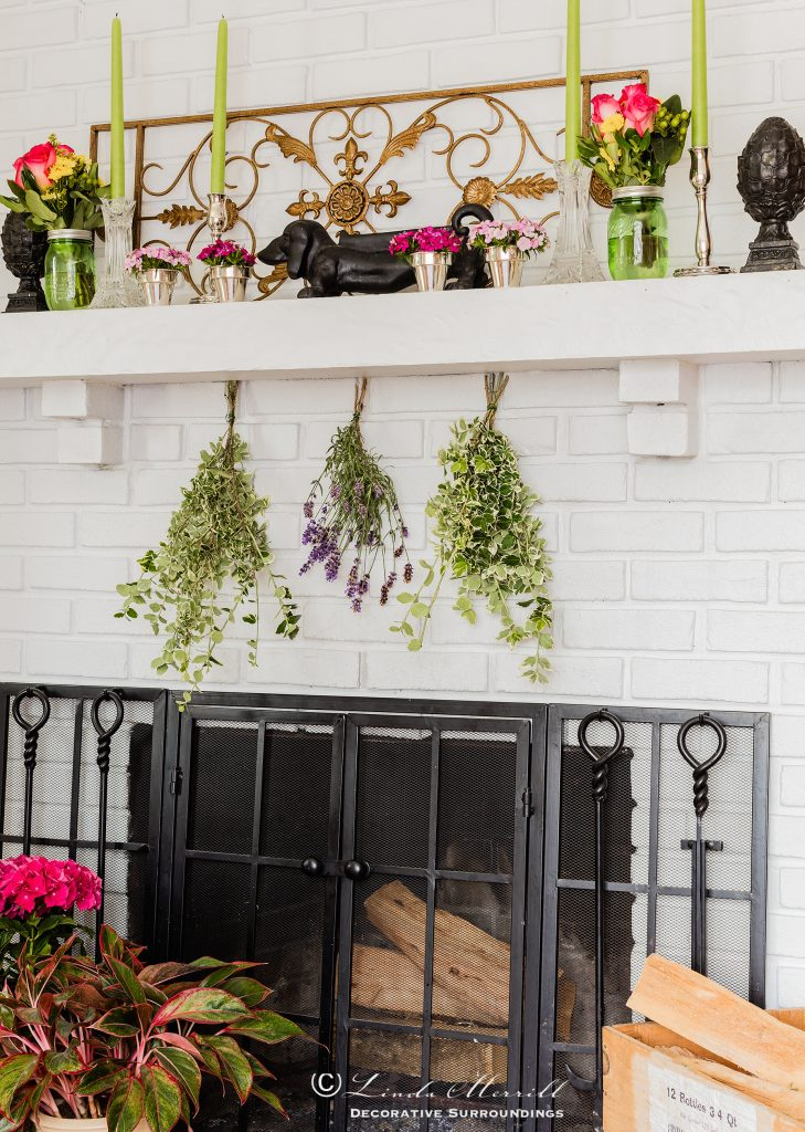 Design by Linda Merrill Decorative Surroundings: Colorful waterfront cottage White brick fireplace with colorful flowers and items on the mantel, black fire screen. Massachusetts 02332