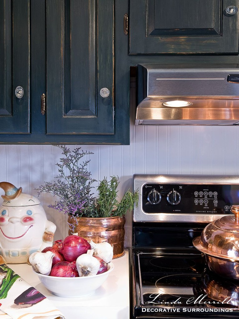 French country kitchen, copper pots, green painted cabinets, stainless steel appliances.