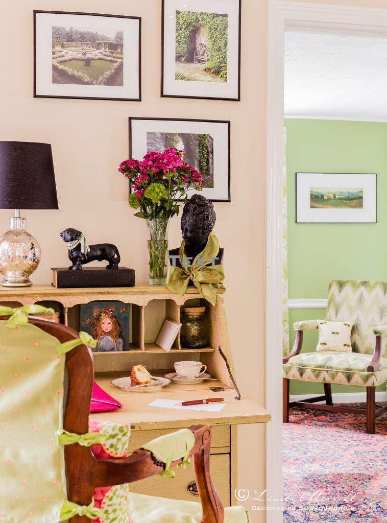 Design by Linda Merrill Decorative Surroundings: Colorful waterfront cottage A small antique green painted desk with French arm chair looking into a room with a green cut velvet upholstered chair.