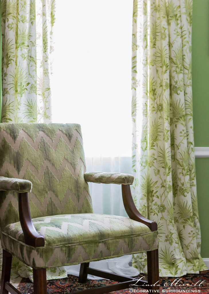 Design by Linda Merrill Decorative Surroundings: Colorful waterfront cottage A green cut velvet upholstered chair sits in front of a window with green and white floral window treatments.