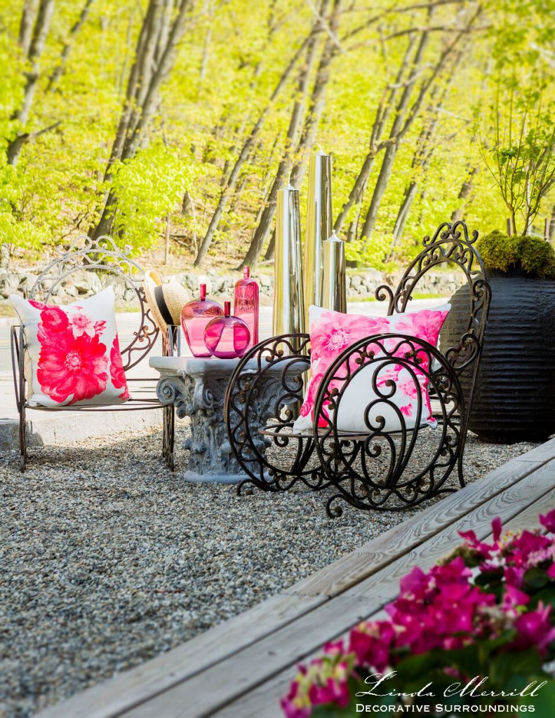 Outdoor sitting area with wrought iron furniture, pink flowers and pillows and glassware