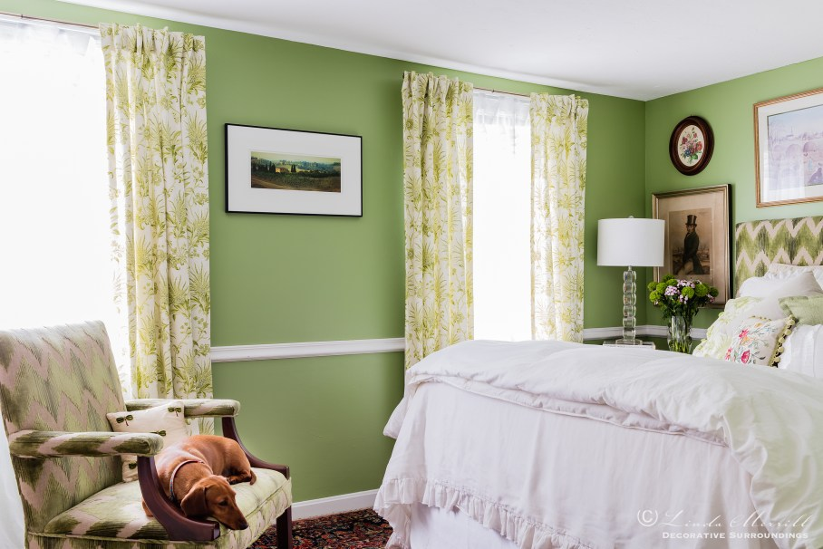 Colorful waterfront cottage A green and white bedroom with upholstered chair and matching upholstered headboard, white linen bedding, dachshund