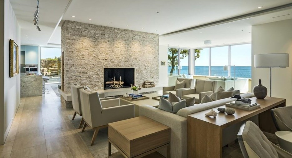 Spectacular oceanside modern beach house in Manchester-By-The-Sea Massachusetts. #modern #beach #coastal #home #oceanside #views #stone #glass #beige #furniture #art #living #room #livingroom
