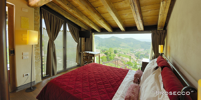 Agritourismo Relais Dolcevista hotel room, red bedding, wood beamed ceiling, large windows with views