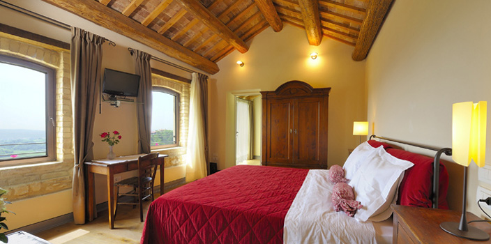 Agritourismo Relais Dolcevista hotel room with red bedding, beamed ceiling, large armoire