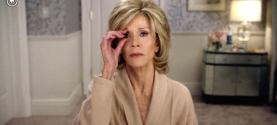 Grace and Frankie Jane Fonda dressing room, soft purple wallpaper white woodworking mirrored cabinet grace removing eyelashes beige dressing gown