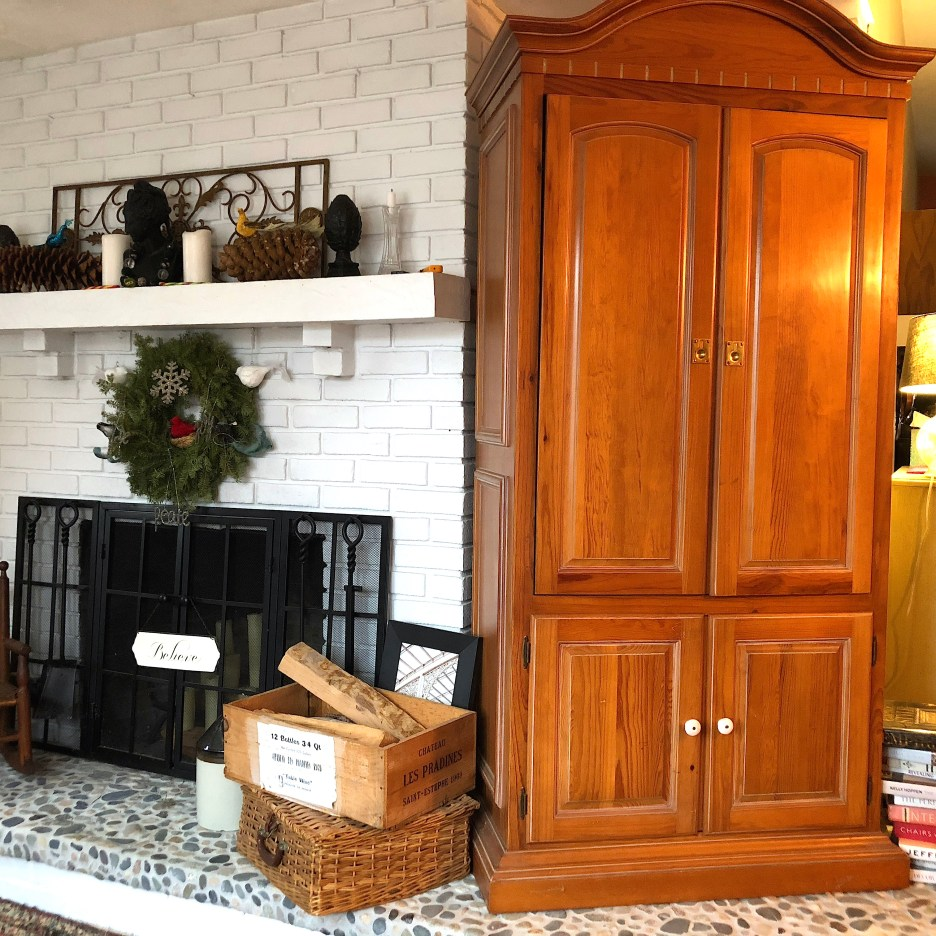 Linda Merrill's white brick fireplace with beach rock hearth and stained pine armoire cabinet