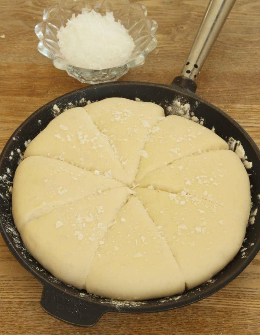 3. Dela degen i åtta bitar med en degskrapa eller kniv. Strö ev. över flingsalt. Låt den jäsa under bakduk i ca 30 min. Sätt ugnen på 250 grader.