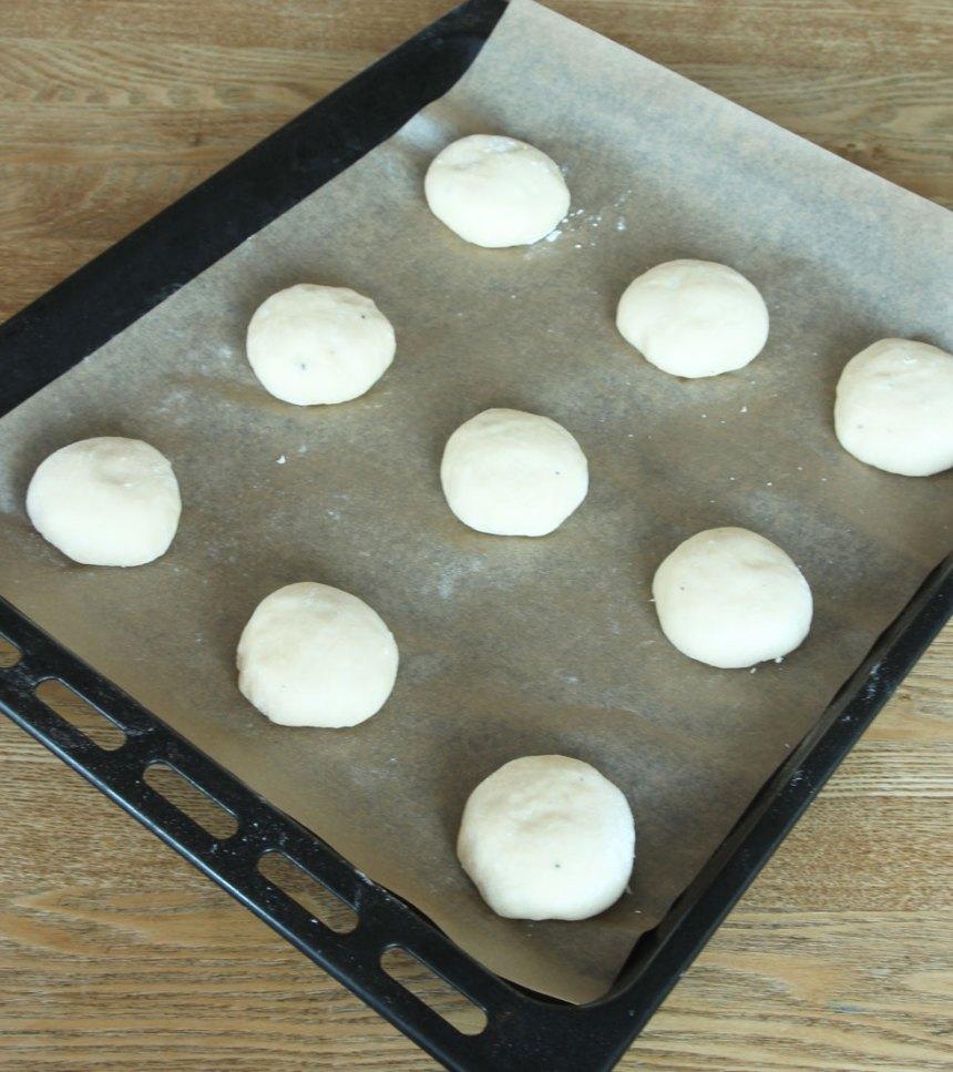 2. Dela degen i 12–14 bitar och rulla bollar av dem. Lägg bullarna på en plåt med bakplåtspapper. Platta till dem lite lätt och låt dem jäsa under bakduk i ca 30 min. Sätt ugnen på 250 grader.