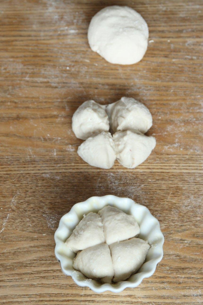 2. Dela degen i 30–34 bitar. Forma runda bullar och skär ett kryss i dem. Lägg dem i muffinsformar av porslin (behöver smörjas) eller papper (behöver inte smörjas). Ställ formarna på en ugnsplåt. Det går också bra att lägga bullarna direkt på en plåt med bakplåtspapper. Låt bröden jäsa under bakduk i ca 30 min. Sätt ugnen på 250 grader.