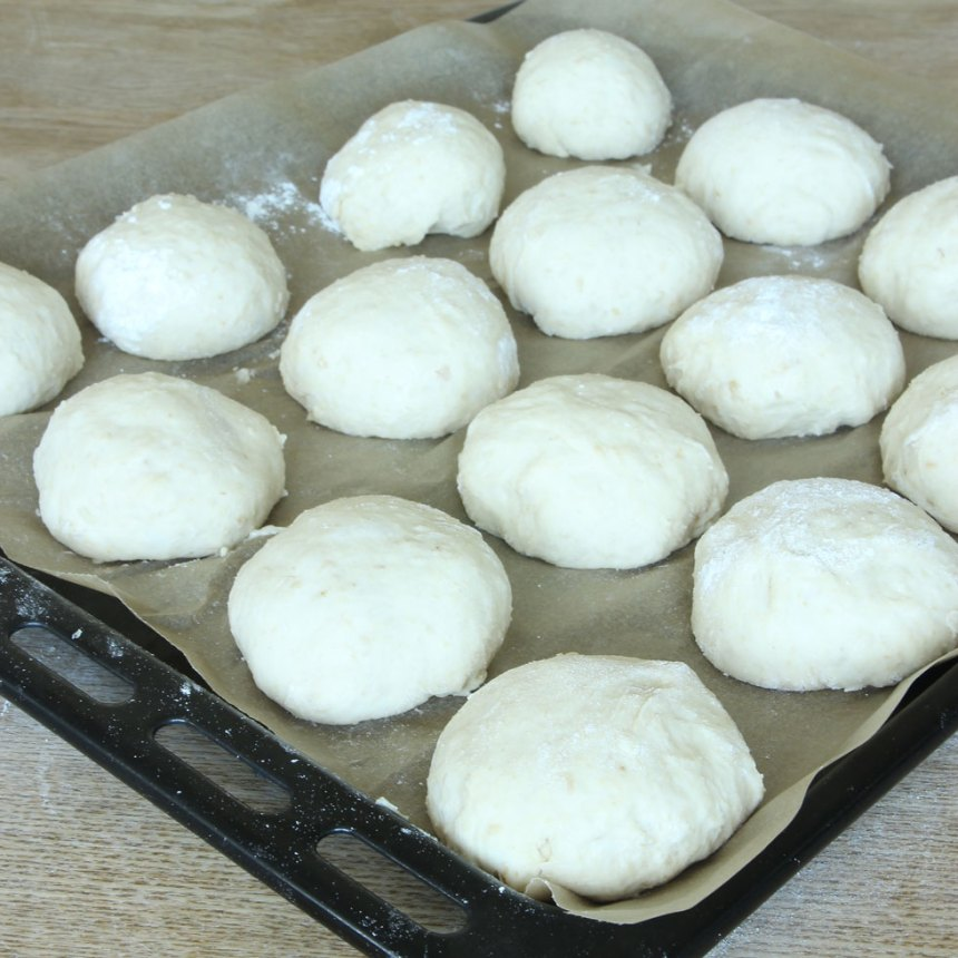 4. Forma dem till runda bollar och lägg dem på en plåt med bakplåtspapper. Platta till dem lite. Låt dem jäsa under bakduk i ca 30 min. Sätt ugnen på 230 grader.