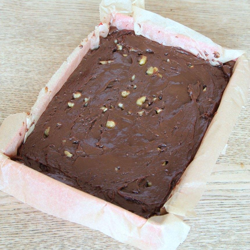 5. Bred ut smeten i en form, 24 x 32 cm, klädd med bakplåtspapper (eller i två mindre formar, ca 12 x 16 cm). Strö över resten av nötterna. Ställ chokladen i kylen för att stelna. Skär kakan i fyrkanter med en vass kniv.