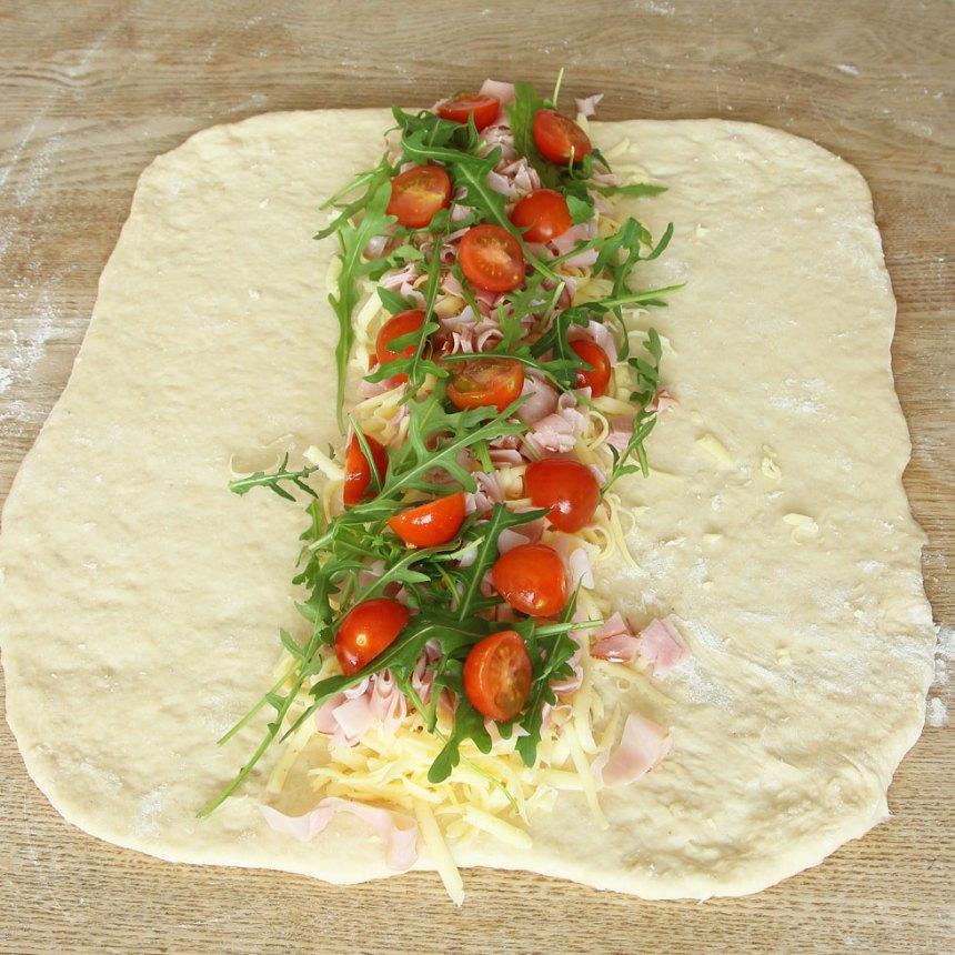 4. Lägg ut ost, skinka, tomater och ruccola i en rad i mitten på degen.