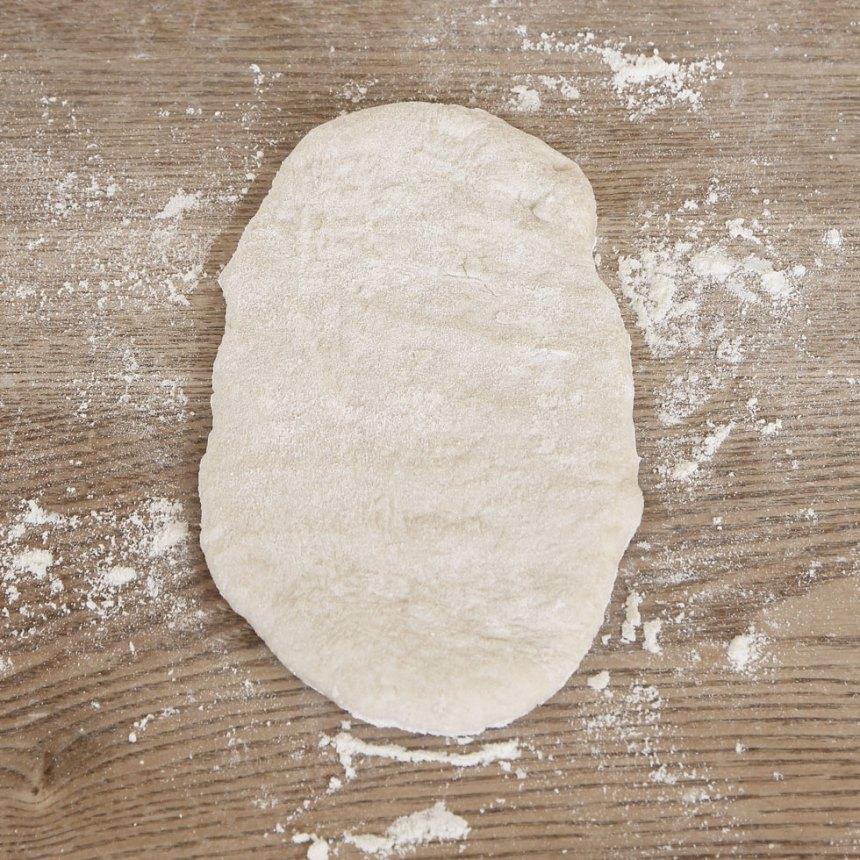 3. Forma avlånga frallor, ca 13 x 8 cm, på ett mjölat bakbord. Strö mjöl på ytan och platta till dem ordentligt.