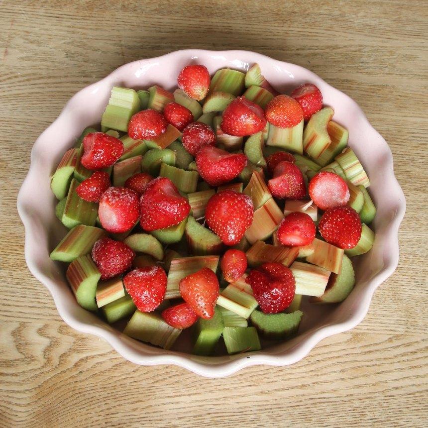 2. Blanda rabarbern och jordgubbarna i en pajform, ca 26 cm i diameter. Strö över strösocker.