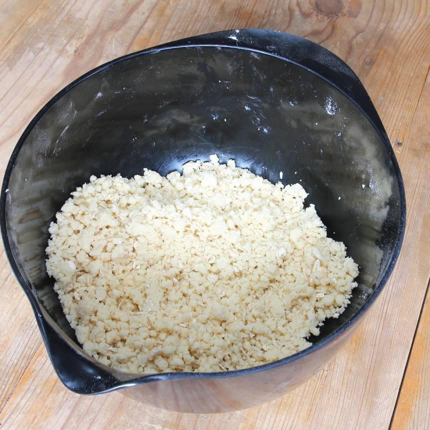 1. Sätt ugnen på 180 grader. Nyp ihop smöret med de torra ingredienserna till en smulig deg.