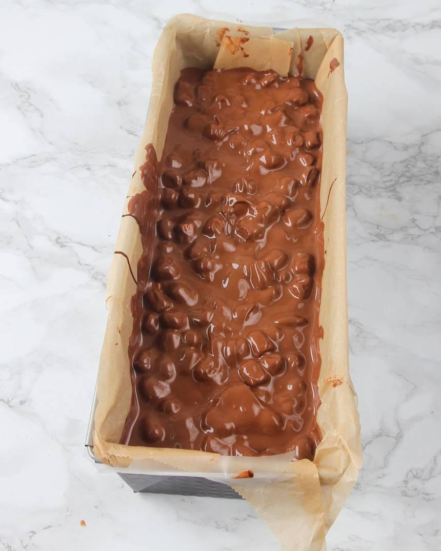 8. Ta fram formen ur kylen. Häll chokladsmeten i formen. Ställ den i frysen en stund tills ytan stelnar.