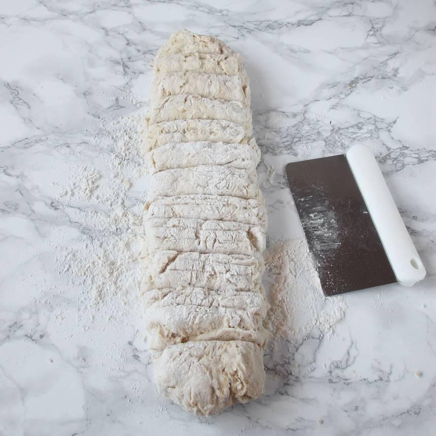 2. Rulla degen i mjöl. Forma degen till en rulle på ett mjölat bakbord. Dela degen i ca 12 bitar.