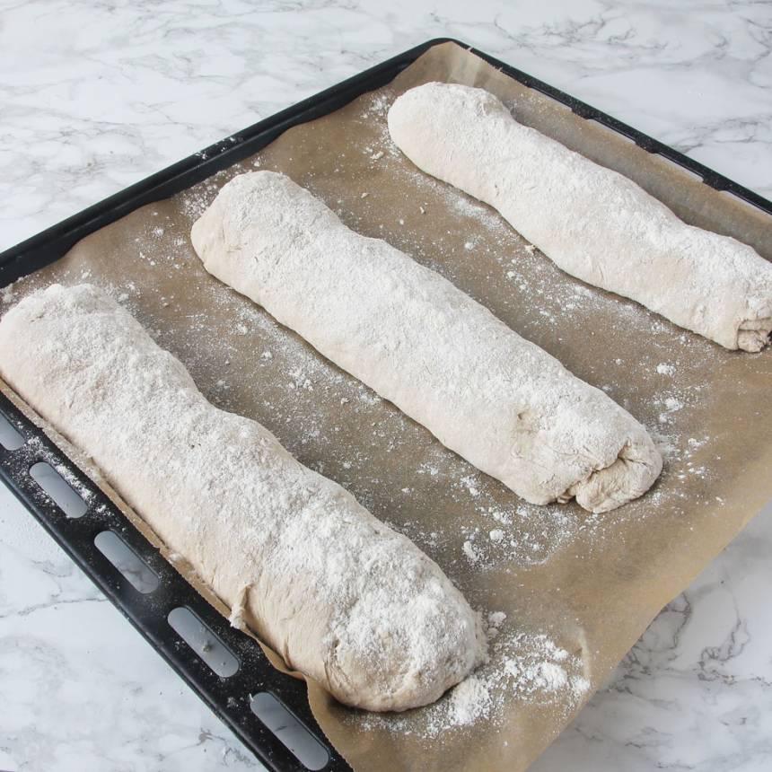 3. Forma degbitarna till längder (lika långa som kortsidan på din ugnsplåt). Rulla dem i lite vetemjöl och lägg dem på en plåt med bakplåtspapper. Låt limporna jäsa under bakduk i ca 30 min. Sätt ugnen på 250 grader.