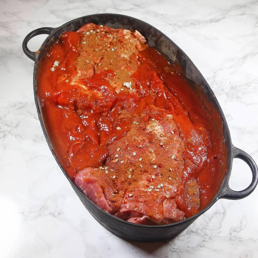 2. Blanda de passerade tomaterna med chilisåsen och häll det runt köttet i grytan.