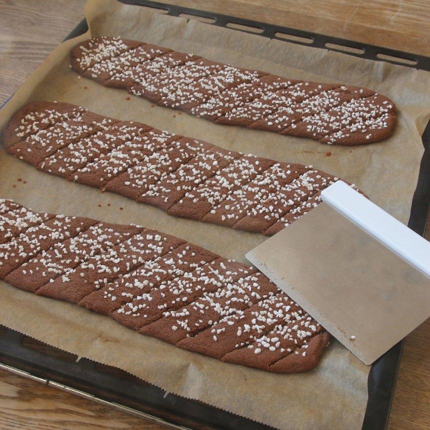 7. Skär längderna i sneda snittar, ca 2 cm breda, med en degskrapa eller kniv direkt när de kommer ut ur ugnen. Låt kakorna kallna och stelna på plåten.