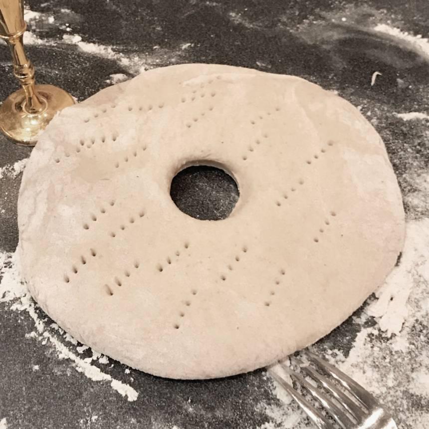 3. Stansa ut ett hål i mitten, ca 4 cm i diameter, med till exempel ett snapsglas. Nagga brödkakorna med en gaffel. Låt dem jäsa under bakduk i ca 30 min. Sätt ugnen på 220 grader.