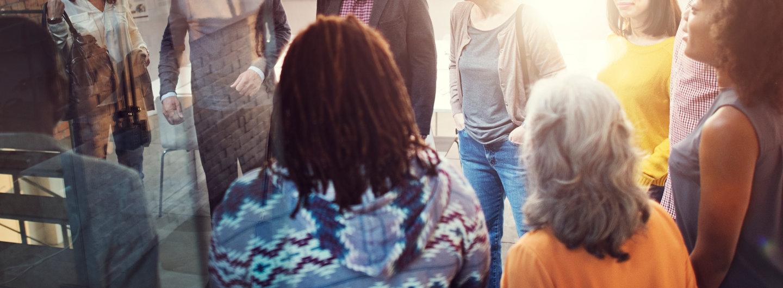 Menschen stehen im Kreis und reden miteinander