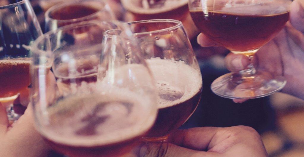 Einander zuprosten mit Biergläsern am Stammtisch