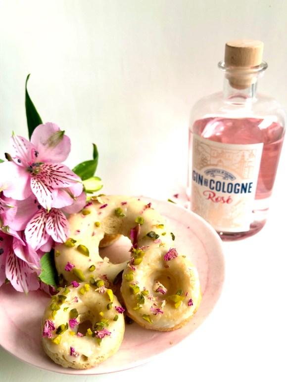 Eine Flasche Gin de Cologne Rosé neben einem Teller mit Backform-Donuts und rosafarbenen Blumen