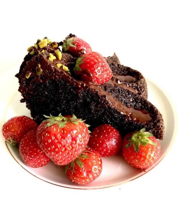 Ein Stück  Brownie-Gugelhupf mit Erdbeeren auf einem cremefarbenen  Teller mit Goldrand