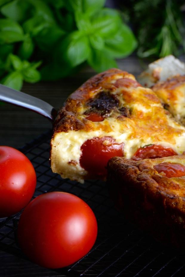 Anschnittfoto der Tomaten-Tarte Caprese, dekoriert mit Tomaten und  Basilikum