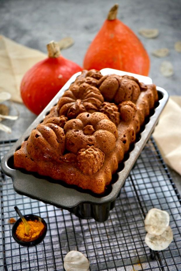 Kastenform mit Kürbis-Gewürz-Kuchen  auf Abkühlgitter mit Kürbissen im Hintergrund